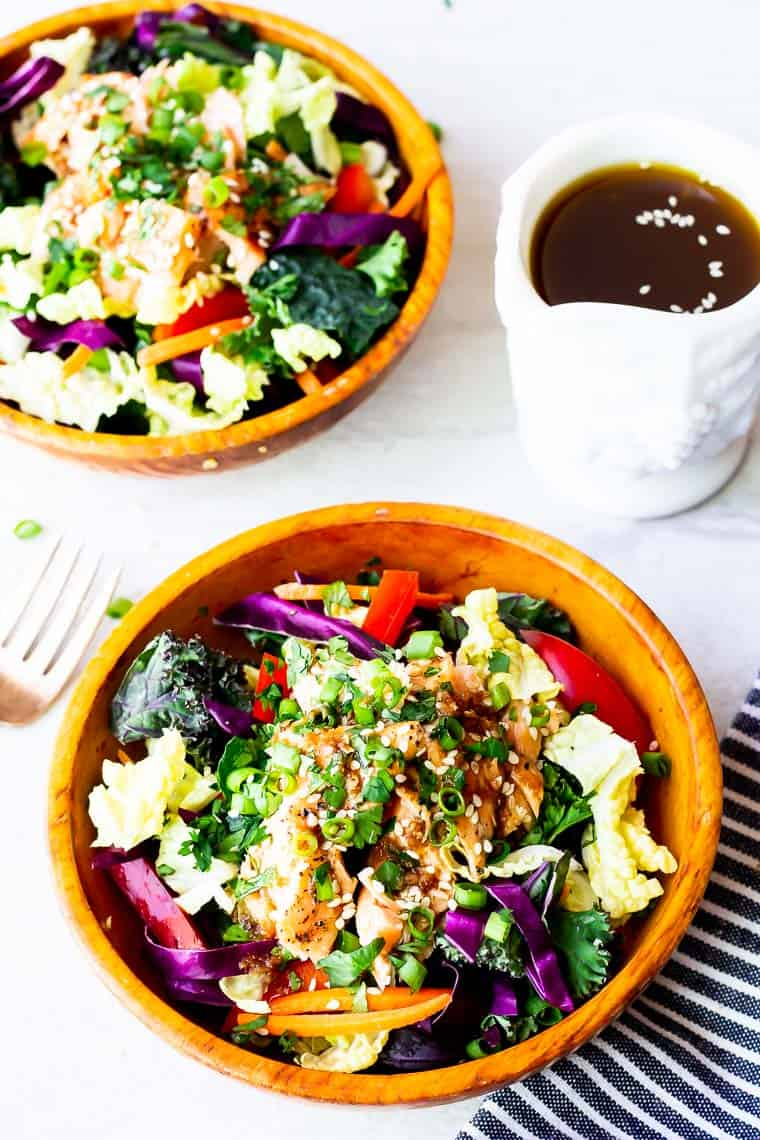 2 bowls of thai salmon salad with a small white pitcher of dressing, a fork, and a blue and white striped napkin in the background over a white backdrop