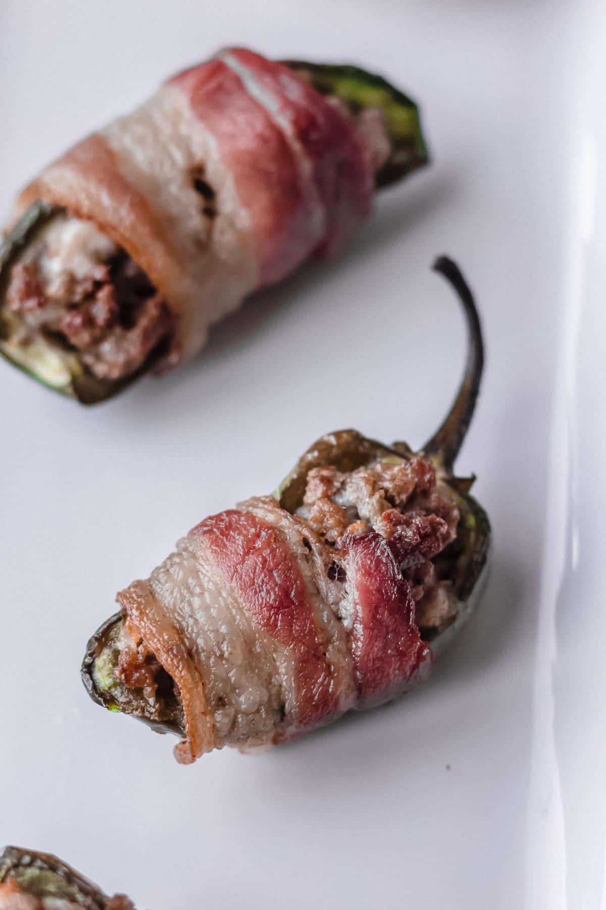 Close up of 2 bacon and blue cheeseburger jalapeno poppers