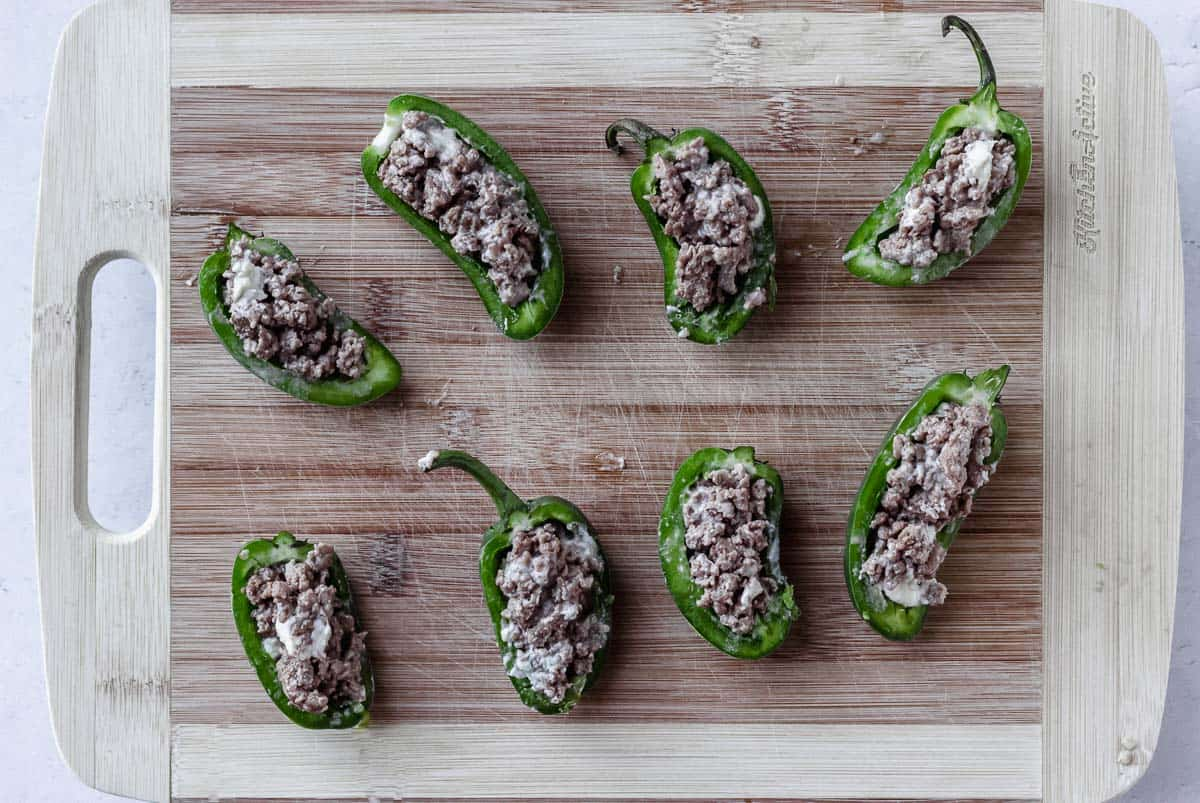 Jalapeno peppers halves filled with ground beef on a wood board