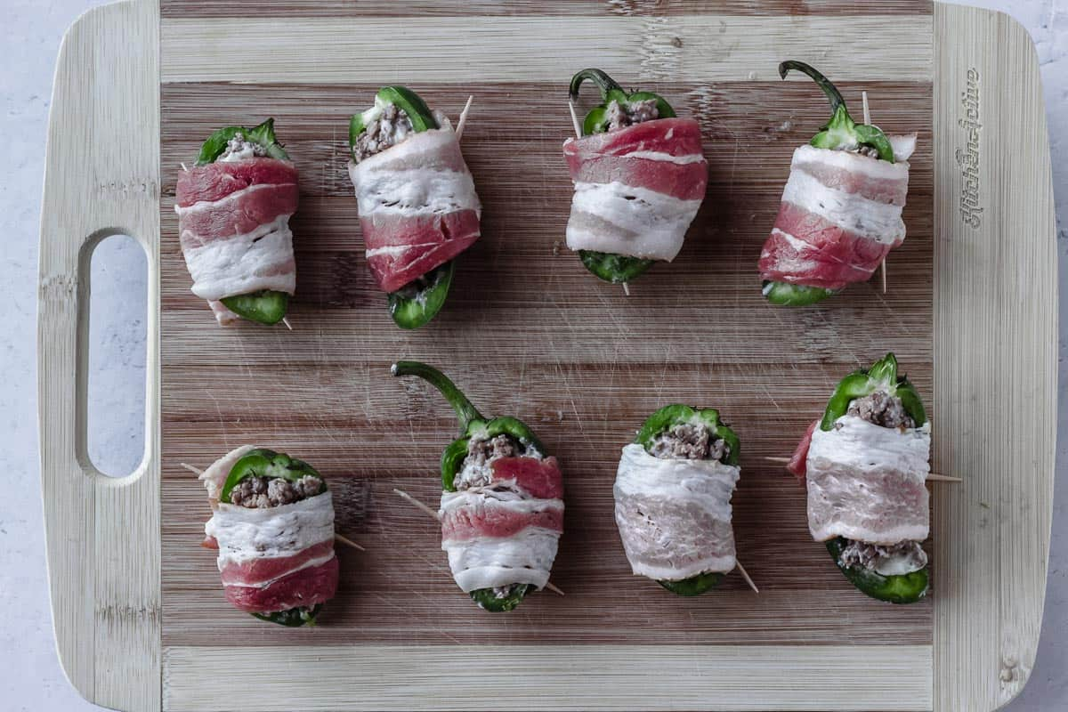 Jalapeno pepper halves on a wood board that are filled with ground beef and wrapped in bacon