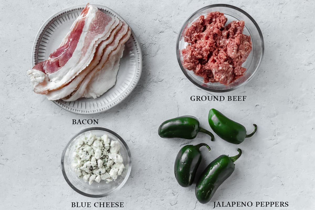 Ingredients to make bacon and blue cheeseburger poppers on a white background with labels.
