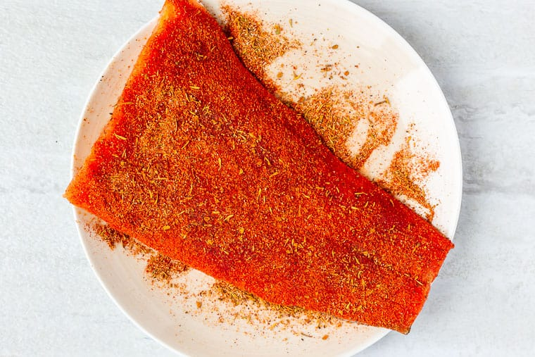 A large piece of salmon coated in blackening seasoning