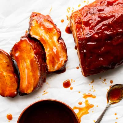 Chipotle Honey-Barbecue Ribs with 3 slices cut off, a dark bowl of barbecue sauce and a spoon on a white background with extra sauce spilled