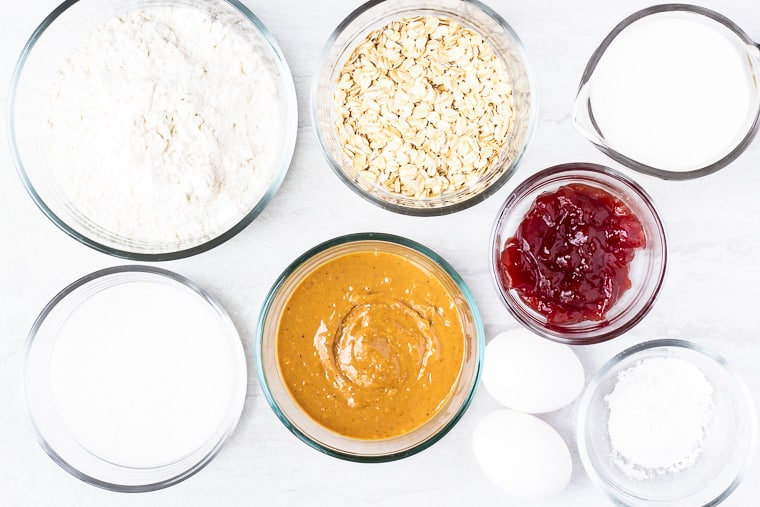 Ingredients to make peanut butter muffins in glass bowls on a white background