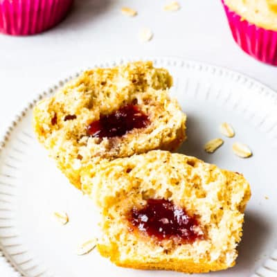 2 muffins halves showing jelly inside with 3 more muffins behind it