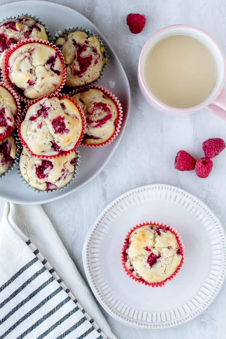 Raspberry Muffins on an off-white serving tray with a single muffin on a white plate over a white backdrop. There is also a cup of tea in a pink mug, a cream and black striped napkin and 4 loose raspberries scattered.