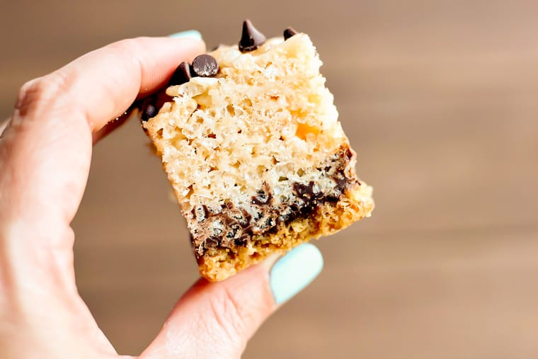 A hand holding up a single S'mores Rice Krispie bar over a wood background