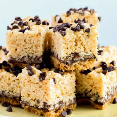 Close up of S'more Rice Krispie Treats stacked on a light yellow plate and a white background
