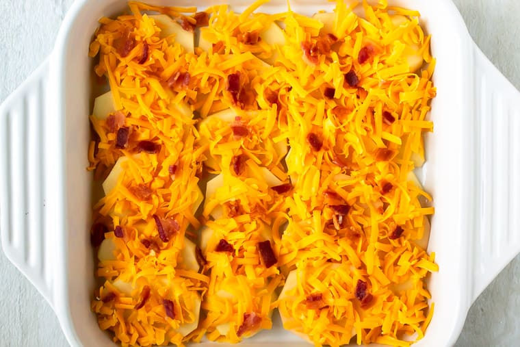 Potato slices covered with shredded cheese and bacon in a white, square casserole dish