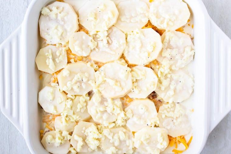 Cream mixture poured over potatoes in a white, square casserole dish