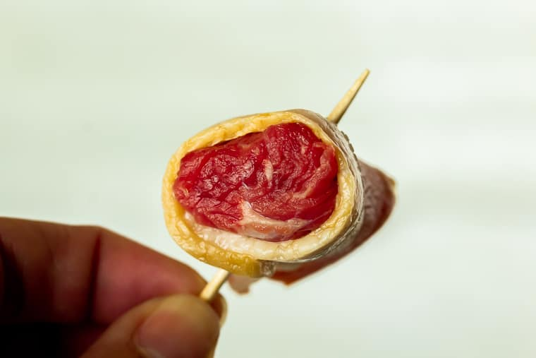 A piece of beef wrapped in bacon secured with a toothpick