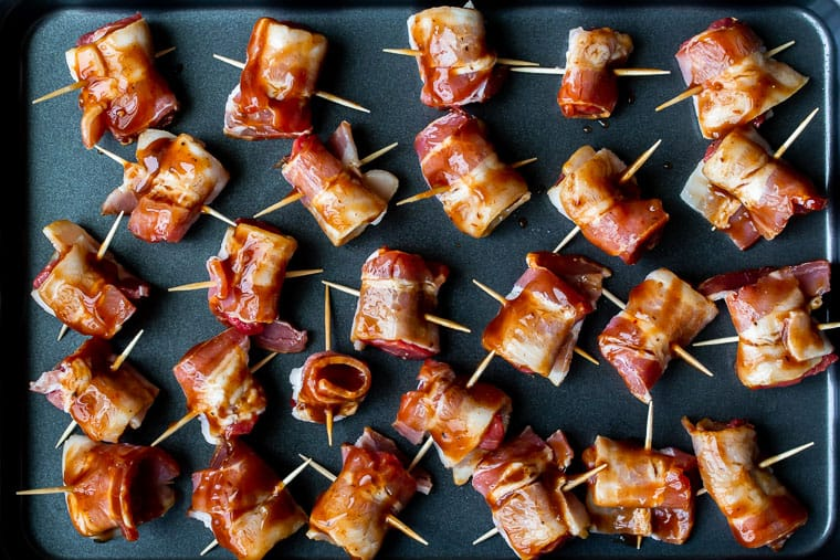 Barbecue steak bites wrapped in bacon on a baking sheet before cooking