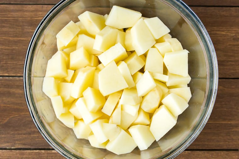 Diced potatoes in a glass bowl on a wood background