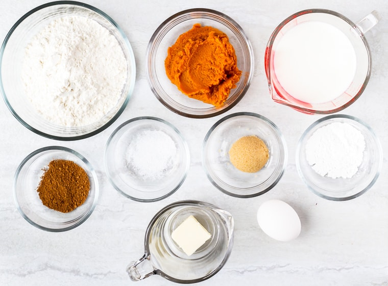 Ingredients needed to make pumpkin spice pancakes in glass bowls over a white background