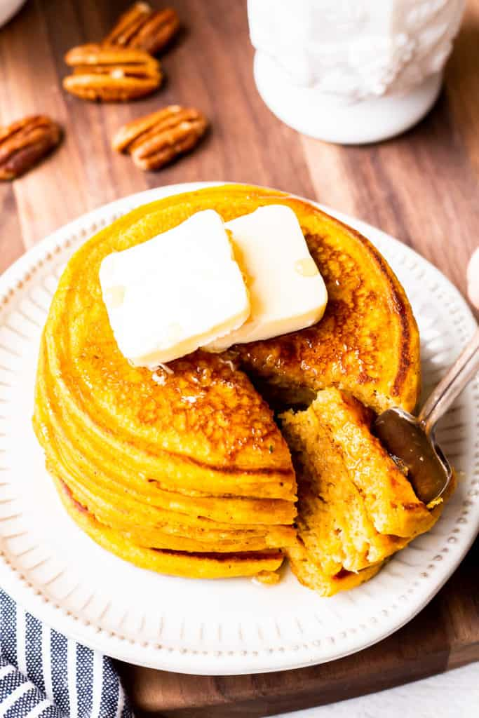 A cut out triangle of a pancake stack on a fork being removed from the pancakes with pecans and a white bowl with maple syrup in the background over a wood board with a blue and white striped napkin partially showing