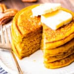A stack of pumpkin spice pancakes on a small white plate with a portion cut out, a fork next to the plate and pecans and 2 white bowls in the background on a white board with a blue and white towel partially showing