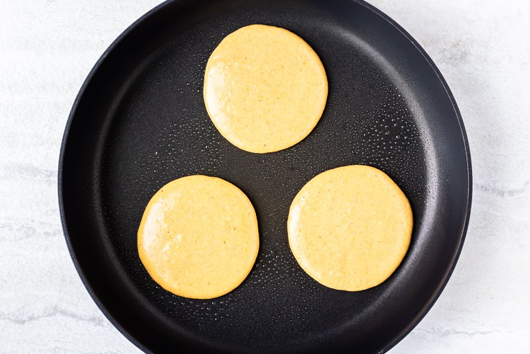 3 pancakes formed with batter in a black skillet over a white background