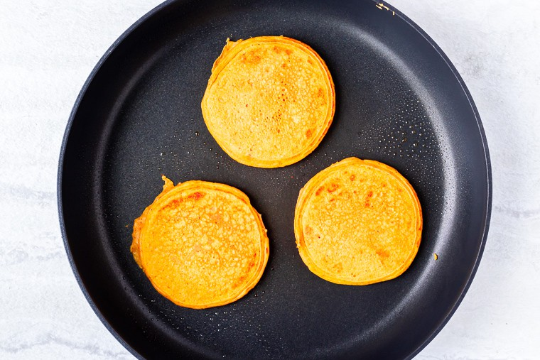 3 cooked pancakes in a black skillet over a white background
