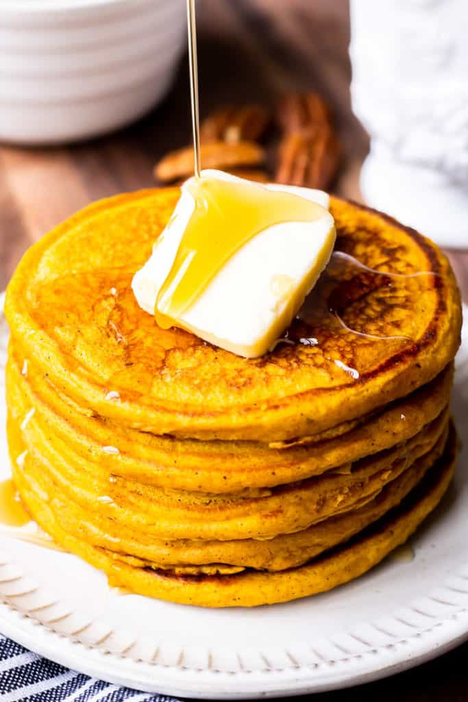 A stack of pumpkin spice pancakes topped with butter with maple syrup being poured over the top with two white bowls in the background on a wood board
