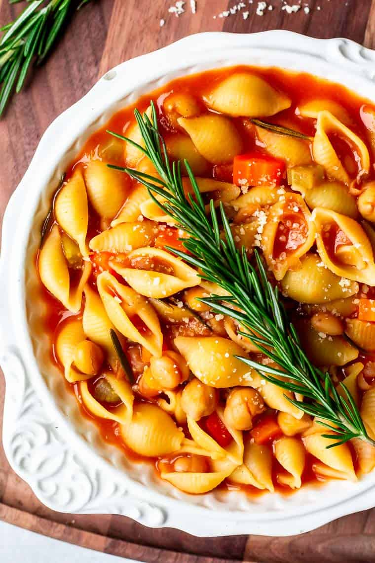 Close up overhead of a white bowl of vegetarian bean soup with pasta with a sprig of rosemary on top over a wood board with grated cheese and more fresh rosemary in the background