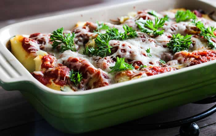 Baked Stuffed Shells Topped with Fresh Parsley in a green casserole dish over a wood table