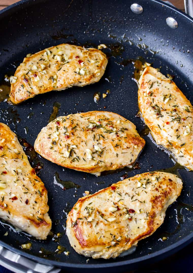 Close up of 5 Garlic Chicken Breasts in a Black Skillet