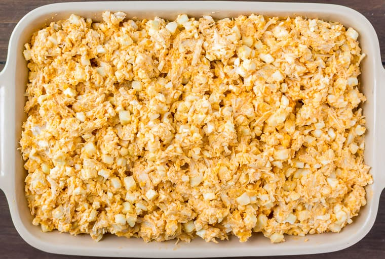 Prepared Buffalo Chicken and Cauliflower Mixture in a rectangular Baking Dish on a wood background