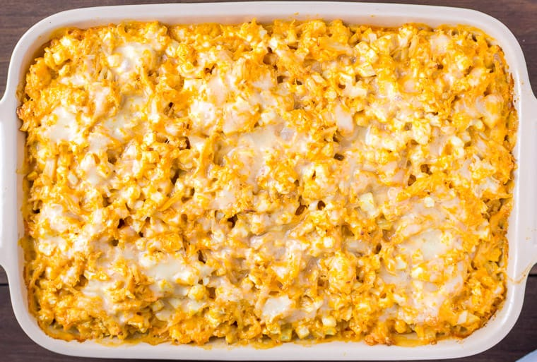 Overhead View of a Baked Buffalo Chicken Cauliflower Casserole in a Rectangular Baking Dish on a Wood Background