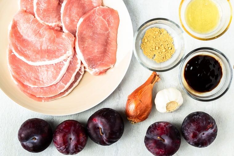 Ingredients needed to make pork in plum sauce in glass bowls or sitting on a white background