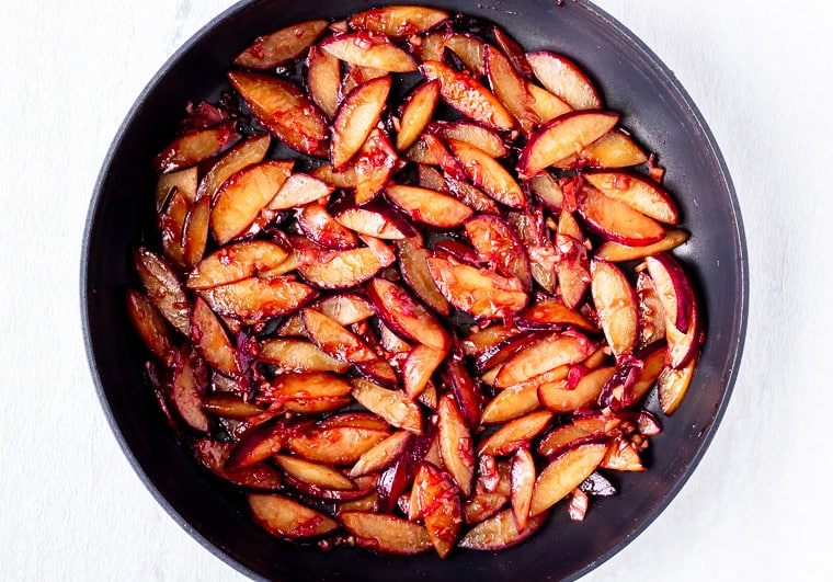 Sliced plums with shallot and garlic cooked in a black skillet over a white background