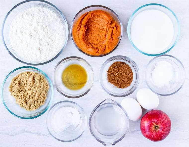 Ingredients needed to make pumpkin apple muffins in glass bowls on a white background