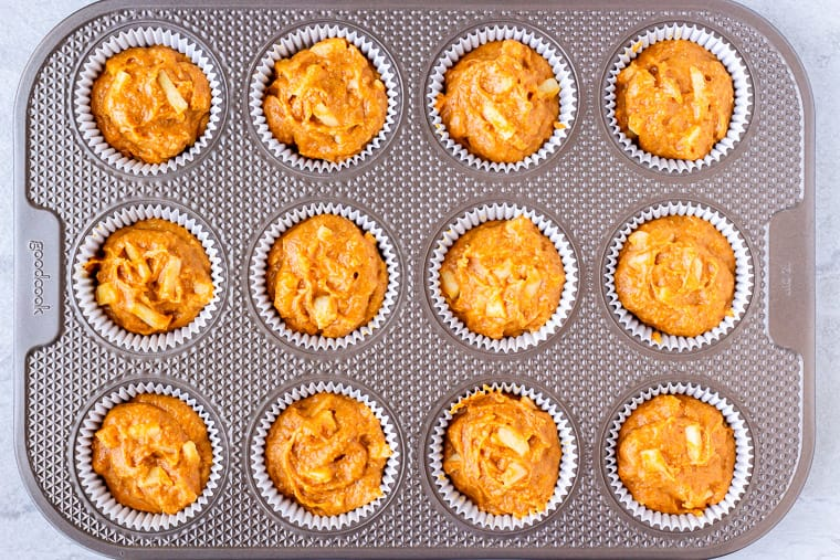 A muffin pan filled with apple pumpkin muffin batter before baking