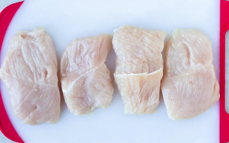 4 turkey cutlets on a white cutting board