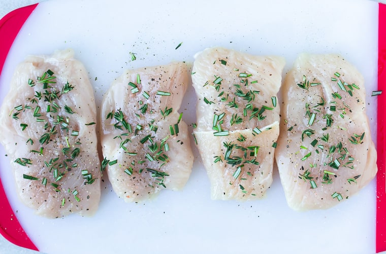 4 turkey cutlets seasoned with fresh rosemary and thyme on a white cutting board