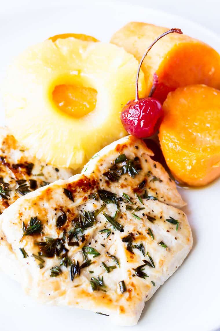 A seasoned turkey cutlet on a white plate with sweet potatoes, pineapple, and a cherry