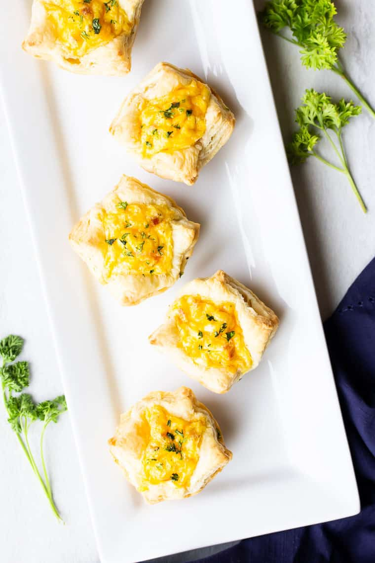Breakfast Puff Pastry Cups on a white rectangular serving tray with a blue napkin and sprigs if parsley around it