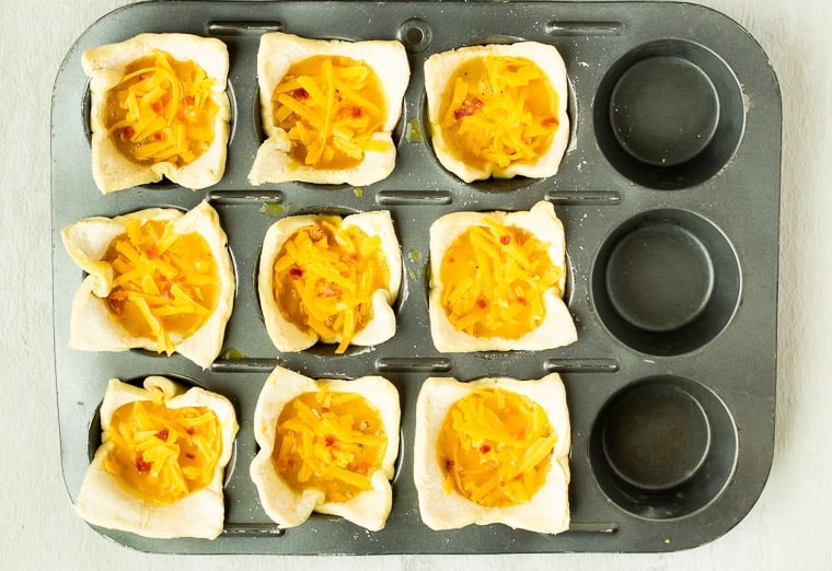 Puff pastry cups filled with bacon, egg, and cheese before baking
