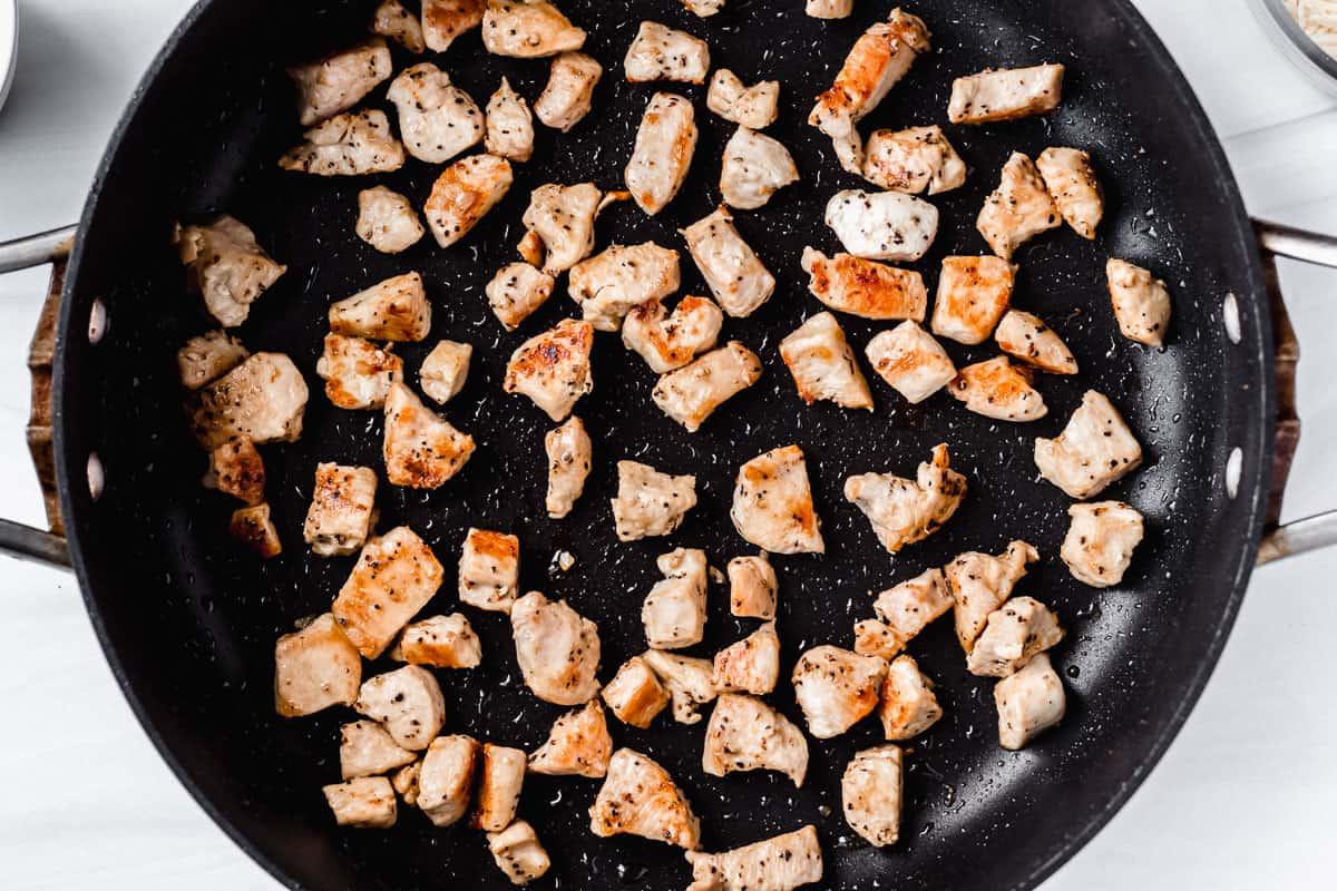 Chicken pieces golden brown in a skillet