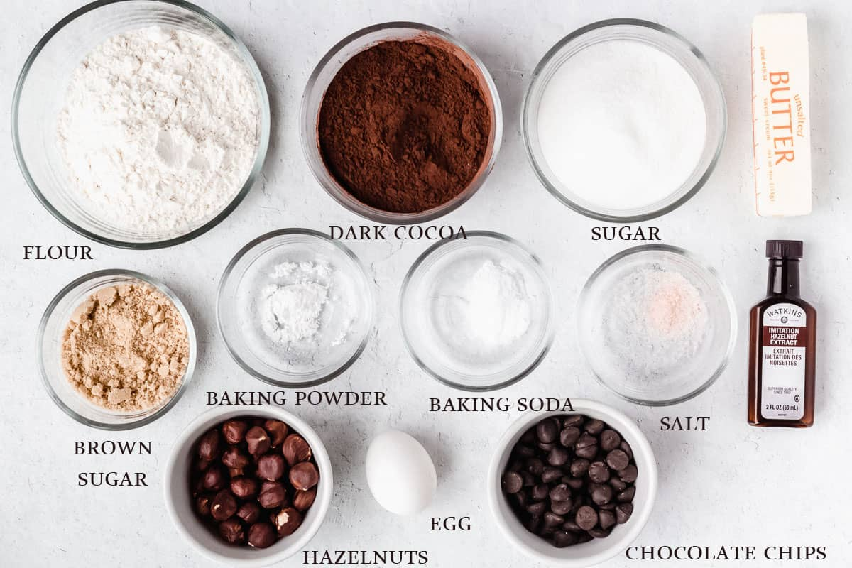 Ingredients needed to make chocolate hazelnut cookies on a white background with labels