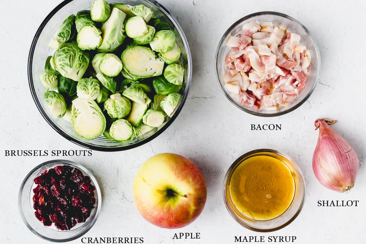 Ingredients needed to make brussels sprouts with bacon, cranberries, and apples on a white background with labels