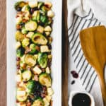 Brussels sprouts on a serving dish with text overlay