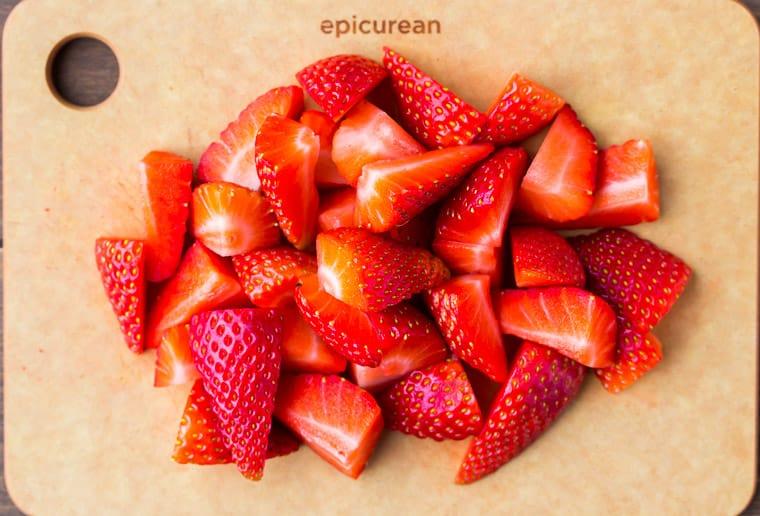 Cut strawberries up close on a wood cutting board