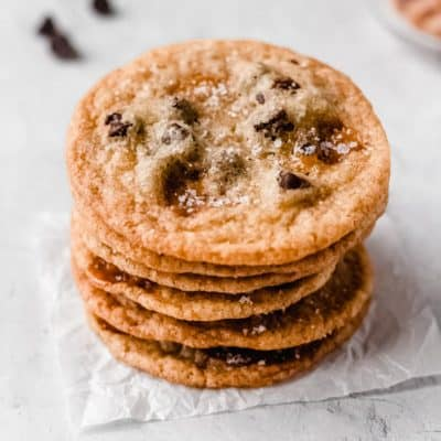 A stack of 6 salted caramel chocolate chip cookies on a white background with chocolate chips around it