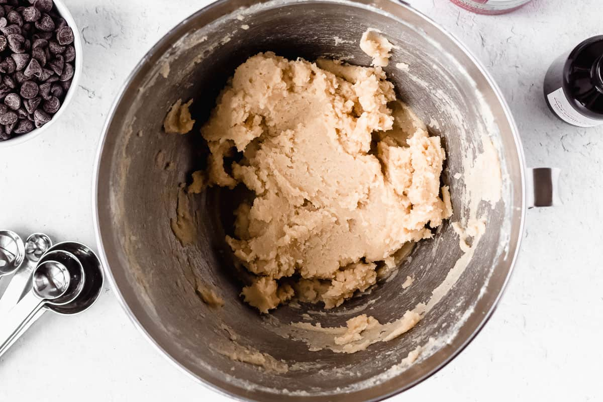 Butter, brown sugar and sugar creamed together in a silver mixing bowl with other ingredients around it