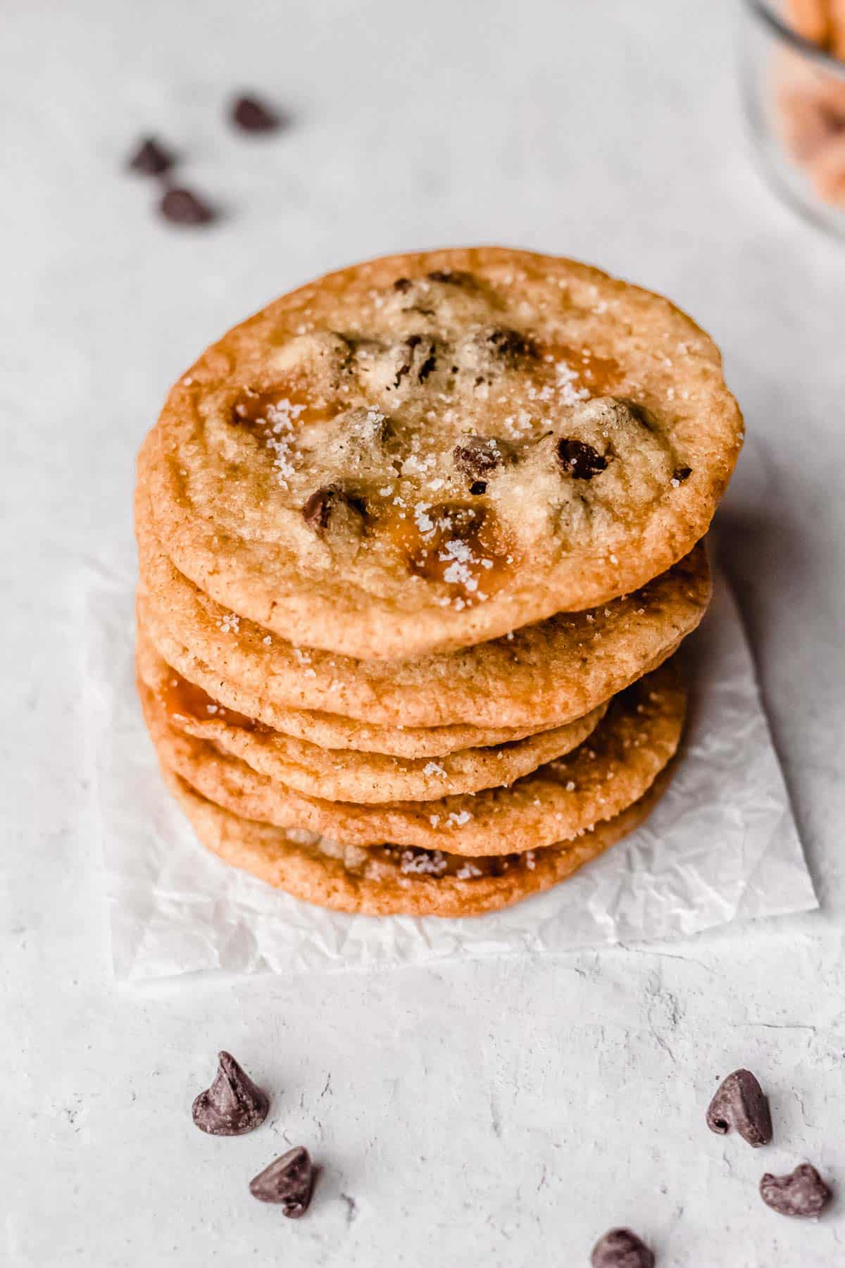A stack of 5 salted caramel chocolate chip cookies on a white background with chocolate chips around it