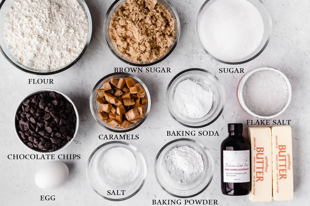 Ingredients to make salted caramel chocolate chip cookies on a white background with a label