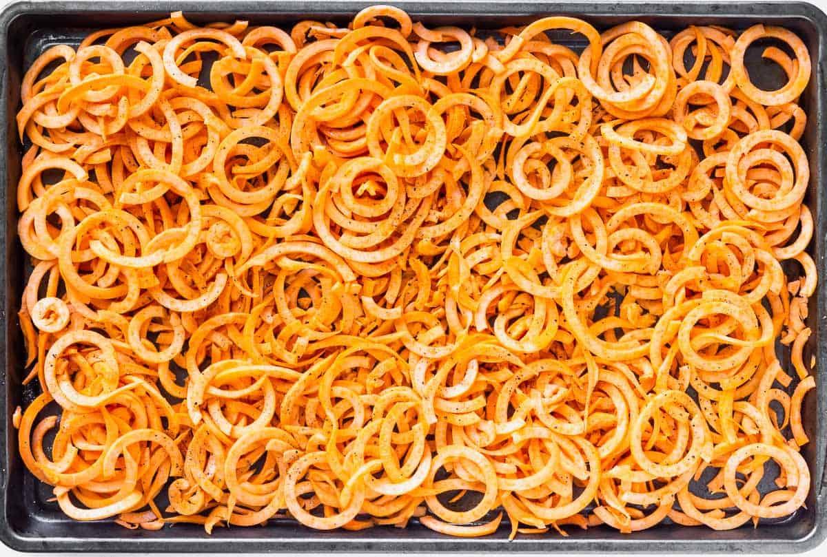 Raw sweet potato noodles on a baking sheet