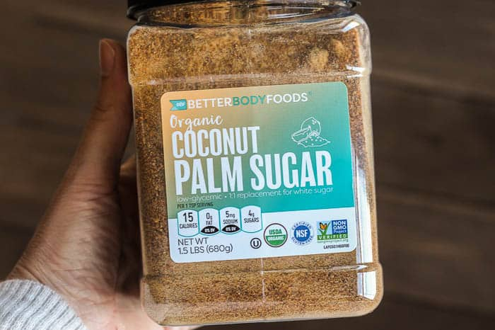 A jar of Coconut Palm Sugar being held up over a dark background