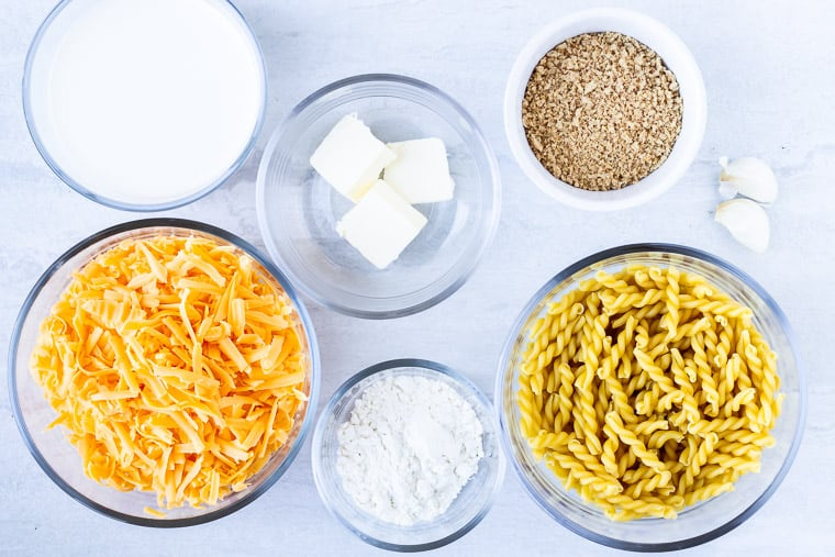 Ingredients needed to make baked mac and cheese in glass bowls on a white background
