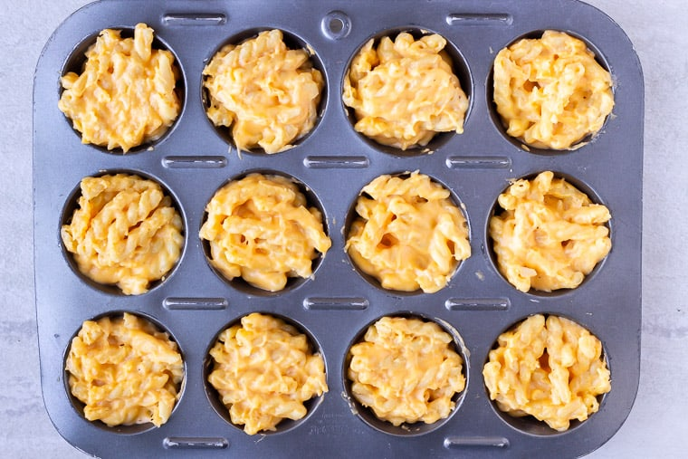 Mac and cheese in a muffin pan before baking